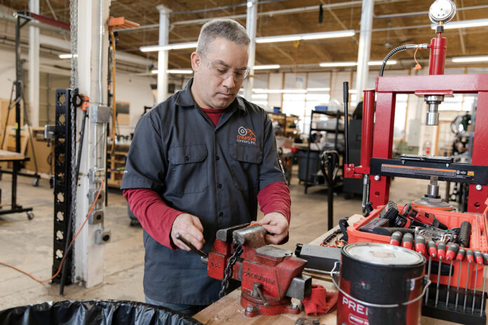 SETTING THE STAGE: Creative Conners Inc. Operations Manager Brian Belfer works on a project at the company's Warren facility. The company specializes in manufacturing controls and chain hoists to aid in moving set pieces for theater productions. / PBN PHOTO/RUPERT WHITELEY