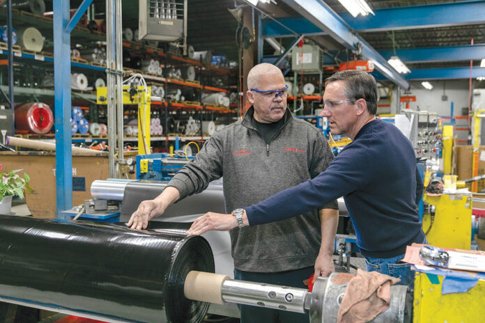 FUELING UP: ­Henrique DaSilva, left, senior lead inspector slitter, and Daniel Dwight, CEO and president of Cooley Group, work together with the company's CoolThane fuel-containment material. / PBN PHOTO/TRACY JENKINS