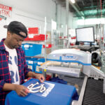 HEATING UP: SquadLocker machine operator Daudi Nabaasa applies a logo to a jersey at a heat-transfer machine at the Warwick company. / PBN PHOTO/DAVE HANSEN