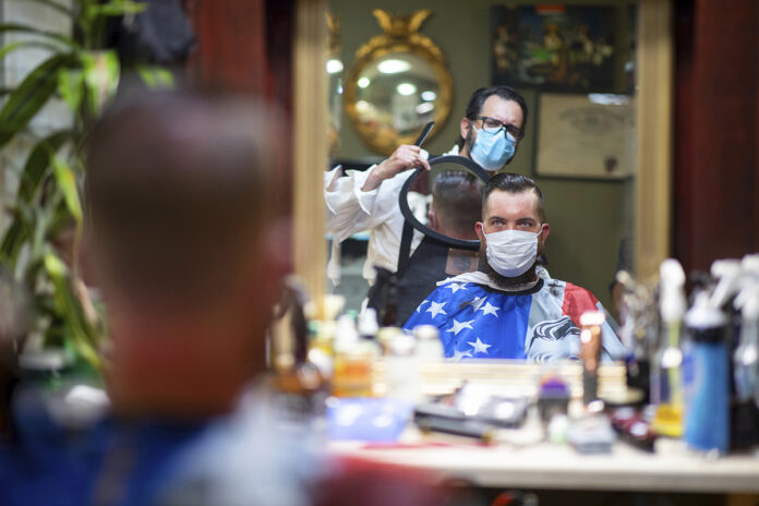 DOUBLE CHECKING: Barber Mike McAndrew holds a mirror as customer Rob Verrastro looks at his new haircut at Three Saints Barbershop and Shave Parlor in Jessup, Pa. Small businesses such as this are desperately trying to stay afloat during the coronavirus crisis, but billions of dollars allocated for aid by Congress may be left on the table. / TIMES-TRIBUNE VIA AP FILE/CHRISTOPHER DOLAN