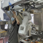 FINE-TUNING: A technician makes an adjustment to a robot at Miso Robotics' White Castle test kitchen in Pasadena, Calif., on July 9. / MISO ROBOTICS VIA AP