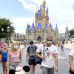 SOME ELBOW ROOM: Visitors to Walt Disney World in Lake Buena Vista, Fla., observe the park's face mask requirements. Labor officials estimate that the Disney parks are only a third full. / ORLANDO SENTINEL VIA AP/JOE BURBANK