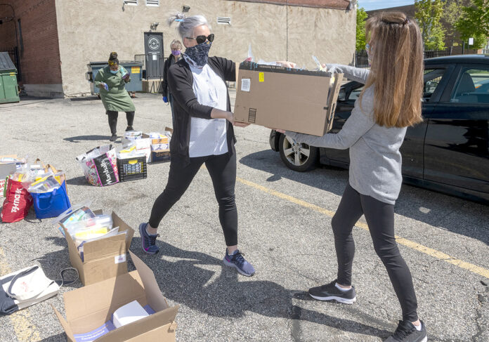 HANDOFF: Inspiring Minds, a nonprofit that works to mentor and tutor students in the Providence area, is delivering books to students during the COVID-19 pandemic. Executive Director Melissa Emidy, left, hands a box of books to Lisa Pierce. / PBN PHOTO/MICHAEL SALERNO