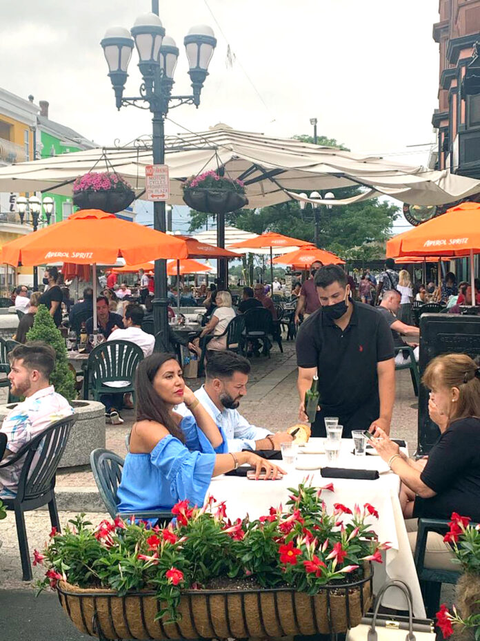 "SAFETY FIRST: A waiter serves diners during an ""Al Fresco on the Hill"" event on Atwells Avenue in Providence. Restaurateurs say stressed staffers are playing the role of enforcers of mask guidelines while keeping an eye out for state inspectors.  / COURTESY FEDERAL HILL COMMERCE ASSOCIATION"