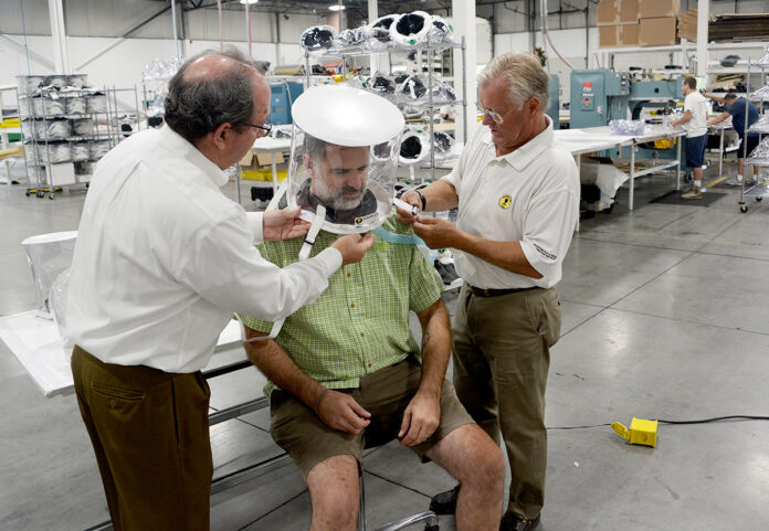 TEAMWORK: Subsalve CEO Richard Heath, left, and Subsalve Chief Growth Officer Richard Fryburg, right, adjust an oxygen-treatment hood on Lombardi Undersea LLC owner Michael Lombardi. / PBN PHOTO/ELIZABETH GRAHAM