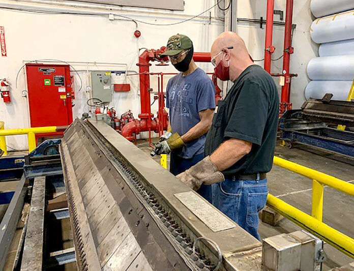 COLLABORATORS: Terry Thompson, left, extruder setup, and Mike Funderburk, master mechanic, team up to perform predictive maintenance on an extruder die at Cooley Group's Pawtucket facility. / COURTESY COOLEY GROUP