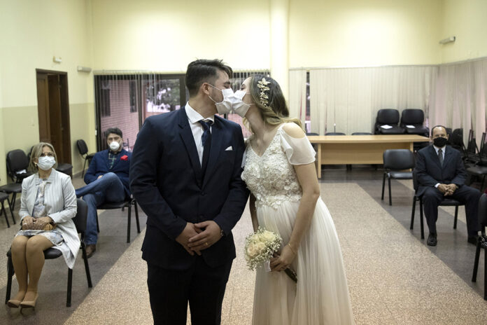 GOING THROUGH WITH IT: Groom Raul Benitez and bride Jenny Bonet wear protective face masks as they kiss during their wedding ceremony at the Civil Registry office, in Asuncion, Paraguay, in June.  / AP FILE PHOTO/JORGE SAENZ
