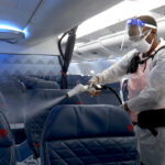 HEAVY DUTY: Melaku Gebermariam uses an electrostatic sprayer to disinfect the inside of a Delta Airlines jet between flights on July 22, at the Ronald Reagan Washington National Airport in Arlington, Va. / AP FILE PHOTO/NATHAN ELLGREN