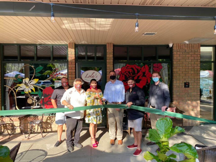 OPENING ACTION: Jodi Ricci, third from the left, and her husband, Michael Mota, fourth from the left, cut the ribbon at the opening of Lola's Lounge and Cantina in Smithfield. Joining them, from left, are Scott Connory, vice president of sales; Joe Ricci, co-owner; Smithfield Town Manager Randy Rossi; and Town Councilman Sean Kilduff. / COURTESY LOLA'S LOUNGE AND CANTINA