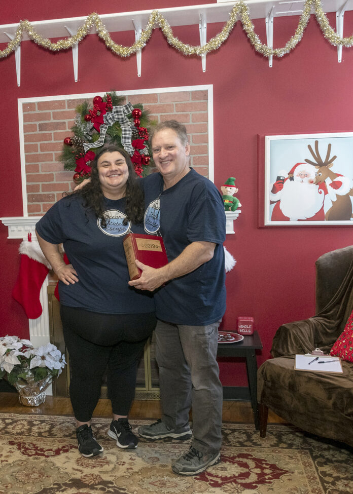 PUZZLE PIECES: Ocean State Escape owner Leonard Albanese, with daughter Rachel. They are in their Christmas-themed escape room in Johnston. / PBN PHOTO/MICHAEL SALERNO