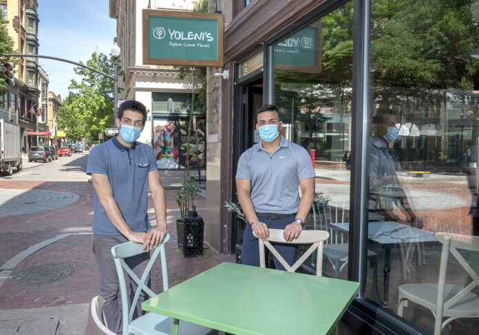 FEELING A LULL: Yoleni's Providence co-owner John Philippides, left, and marketing manager Danny Willis say lunchtime business at the Greek restaurant and marketplace has suffered because fewer workers have been in downtown Providence offices during the pandemic.  / PBN PHOTO/MICHAEL SALERNO