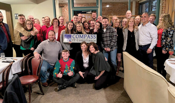 HOLIDAY SPIRIT: Compass IT Compliance LLC employees gather during a Christmas party. COURTESY COMPASS IT COMPLIANCE LLC