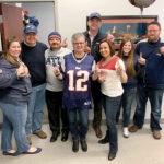 FOOTBALL FEVER: Secure Future Tech Solutions employees wear New England Patriots attire as part of a recent Patriots Spirit Day at the office. COURTESY SECURE FUTURE TECH SOLUTIONS