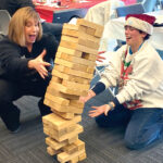 GAME DAY: Narragansett Bay Commission Executive Director Laurie Horridge, left, and Liz Kohr enjoy a game of Jenga at a holiday employee appreciation event. / COURTESY NARRAGANSETT BAY COMMISSION
