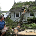 DAVID HAIGH looks at a large tree that fell on his home on in Pembroke, Mass on Wednesday, Sept. 30, 2020 after a storm passed the area. The National Weather Service reported that winds gusted as high as 72 mph near Boston at around 7 a.m. Wednesday before leveling off through the morning. / AP FILE PHOTO/JOHNVTLUMACKI/THE BOSTON GLOBE