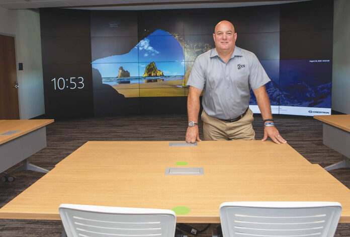 BIG SCREEN: Bob Mathews, account manager for CCS Presentation Systems New England, stands in front of a large 24-cube video wall within the engineering emerging technologies lab inside the new School of Engineering at Roger Williams University. / PBN PHOTO/KATE WHITNEY LUCEY