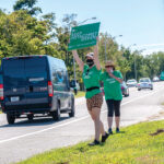 SIGN OF THE TIMES: Members of Keep Metacomet Green! attempt to drum up support recently outside the entrance to the Metacomet Golf Club, the site of a proposed residential and commercial development. / PBN PHOTO/MICHAEL SALERNO