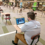 PLENTY OF ROOM: Tucker Quinn, a political science major from Warwick, studies alone at the Community College of Rhode Island in Warwick recently. Not many students are attending in-person classes in the fall semester. / PBN PHOTO/MICHAEL SALERNO