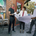 MAPPING IT OUT: From left, Ricky Bernard, co-owner of Island House Restaurant; Providence Revolving Fund Executive Director Carrie Zaslow; and Project Manager Thomas D'Ovidio go over a map outside of Bernard's establishment.  / PBN PHOTO/RUPERT WHITELEY