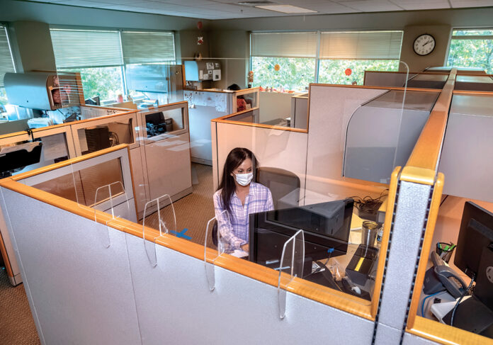 SOME BREATHING ROOM: Collection specialist Dosha Bogosian works in a sparsely populated office at XRA Medical Imaging in Cranston. While XRA's diagnostic services have remained open for months, more of the administrative workers have returned but are keeping their distance from one another.  / PBN PHOTO/MICHAEL SALERNO