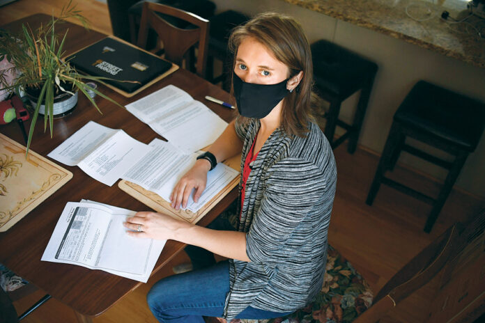 THE PAPER TRAIL: Melissa Szymanski sits with some of her medical bills at home in Glastonbury, Conn. Szymanski got sick earlier this year and wound up with a $3,200 bill because she wasn't diagnosed initially with COVID-19. Later, tests showed she had it, and she is fighting to have her bills reduced. / AP PHOTO/JESSICA HILL