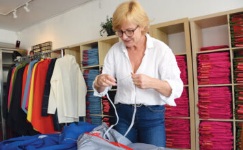 GLOBAL VIEW: Susan Mocarski, founder and owner of Cleverhood LLC, prepares some of the apparel her company manufactures for her store in Providence. With slumping sales in the U.S. because of the pandemic, she's put more of her focus on boosting sales abroad. / PBN PHOTO/ELIZABETH GRAHAM