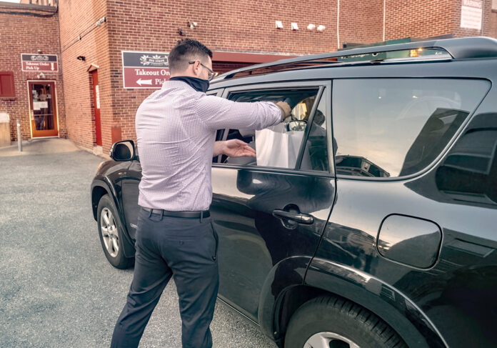 TAKEOUT: Red Stripe in Providence is a city neighborhood restaurant that doesn't have a drive-thru, but it has converted its back door into something approximating one. General Manager Mike Marchezzo delivers an order to Bill Heindel, of Providence. / PBN PHOTO/MICHAEL SALERNO