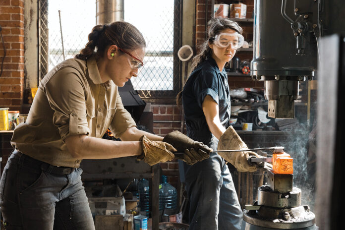 HEATING UP: Alaina Mahoney, left, of Providence-based A.M. Design & Fabrication LLC, works with assistant Erica Compton heating metal in a forge to hammer out a mirror frame for Mahoney's upcoming product line release.  / COURTESY RUE SAKAYAMA PHOTOGRAPHY