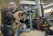 PUMPING OUT PRODUCT: The Bosworth Co.'s machine shop supervisor, who asked not to be named, uses a drill press to tap holes into the aluminum body of the Guzzler diaphragm pump. CEO and President Douglas Reilly, not pictured, said the East Providence pump manufacturer saw an increased demand for the Guzzler, a small, foot-operated pump used in portable sinks and hand-wash stations, during the coronavirus pandemic. / PBN PHOTO/ELIZABETH GRAHAM