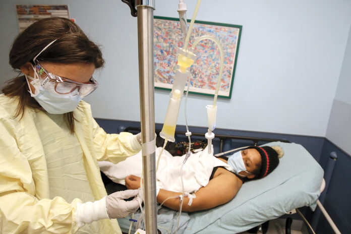 CLOSE WATCH: Registered nurse Jessica Pace, left, who works in the Rhode Island Hospital and Hasbro Children's Hospital Emergency Department, checks the intravenous line of Dolce Contreras, 32, of Central Falls, who is receiving convalescent plasma therapy as part of a clinical trial on its effectiveness against COVID-19. / COURTESY LIFESPAN CORP./WILLIAM MURPHY