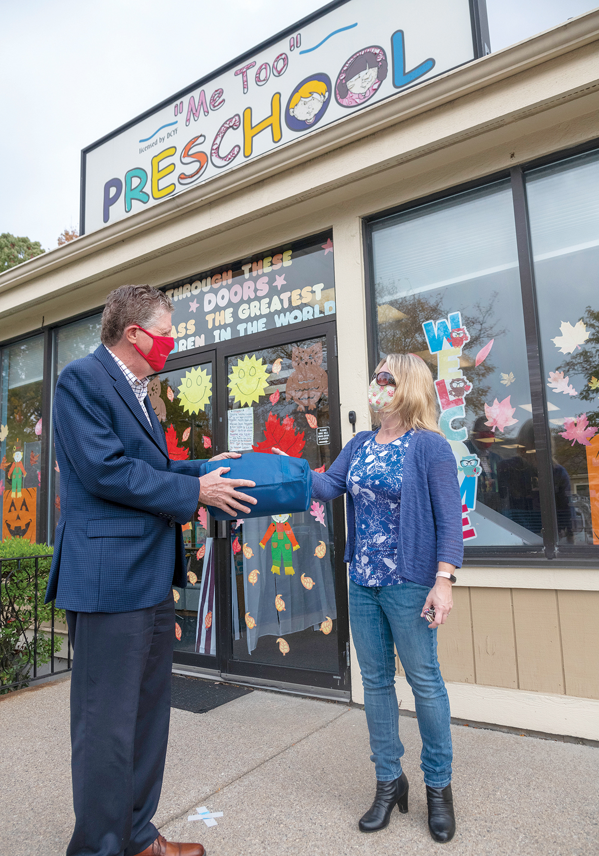 DELIVERY MAN: Lt. Gov. Daniel J. McKee meets with Kim Fortier, co-owner of Me Too Preschool in Woonsocket, as part of his effort to get businesses to apply for the Restore RI grant programs. He is also delivering face masks. / PBN PHOTO/MICHAEL SALERNO