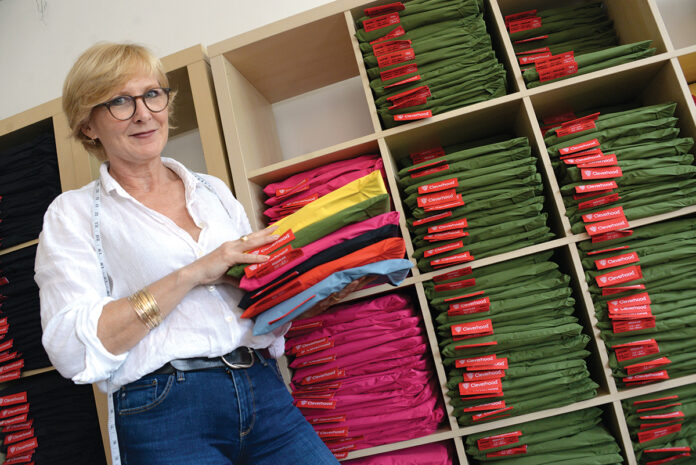STOCKED UP: Susan Mocarski, owner and principal designer of Cleverhood LLC, checks the inventory in the company's Providence retail store. / PBN PHOTO/ELIZABETH GRAHAM