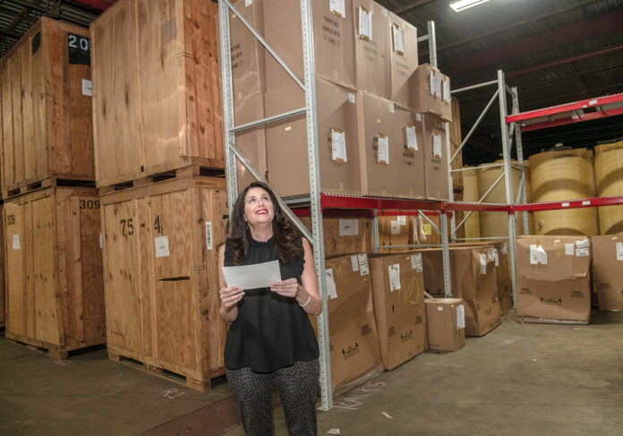 ON THE MOVE: Christine Crum, owner of Gentry Moving and Storage, makes her way around the company storage facility. / PBN PHOTO/MICHAEL SALERNO