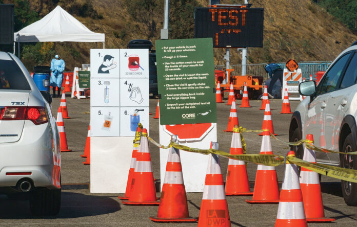 READY AND WAITING: Instructions to perform a COVID-19 virus self-test are displayed for drivers outside Dodger Stadium in Los Angeles. The site can handle 6,000 tests in a day. With sites such as this already operating nationwide, experts say there are reasons to think the U.S. is better able to deal with a surge in cases. / AP FILE PHOTO/DAMIAN DOVARGANES