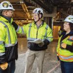 SITE MANAGEMENT: Gilbane Inc. CEO Michael McKelvy, center, speaks with Dauris Nunez, left, and Nury Ruiz during construction of the Twin River Tiverton Casino Hotel. / COURTESY GILBANE INC.