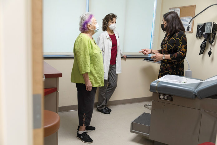 ESSENTIAL SERVICE: The Rhode Island Free Clinic has provided more than 40,000 free patient visits to uninsured, low-income adults over the last five years. CEO Marie Ghazal, right, speaks with primary care provider Marina Rodriguez, center, and psychiatric clinical nurse specialist Sylvia Weber.  / PBN PHOTO/RUPERT WHITELEY