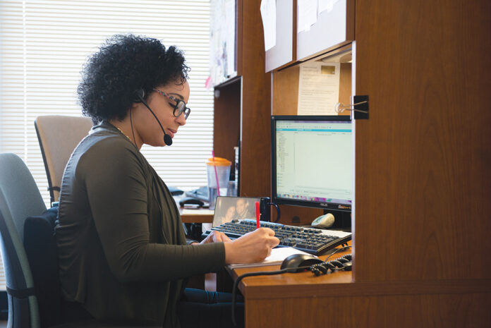 ON THE LINE: United Way of Rhode Island Call Center Manager Evelyn Cabrera takes a call at the organization's office in Providence.  / COURTESY UNITED WAY OF RHODE ISLAND