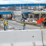 "UP-ROUTED: Construction workers are on-site at the Westminster Street overpass, part of the Route 6-10 connector project in Providence. Visible in the background is the ""flyover"" bridge, a major feature of the new design for the busy exchange.  / PBN PHOTO/MICHAEL SALERNO"