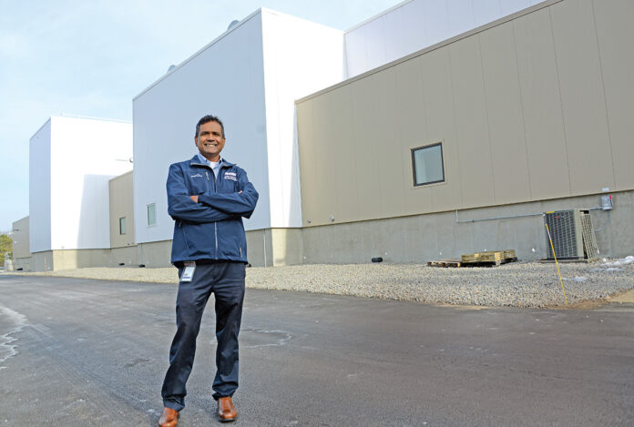 R.I. EXPANSION: Rohan Persaud, plant manager and executive director at Amgen Rhode Island, stands outside the company's new next-generation biomanufacturing plant in West Greenwich. He is overseeing the startup and licensing of the facility.  / PBN PHOTO/ELIZABETH GRAHAM