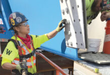 PIECING IT TOGETHER: Aetna Bridge Co. ironworker Lisa Silvio helps install bolts on a bridge under construction above the Route 6-10 connector in Providence.  / COURTESY LISA SILVIO