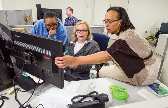 PROBLEM-SOLVING: Amica Mutual Insurance Co. employees, from left, Kimberly Meriweather, Keila Bianco and Esther Garcia work together at a computer station at the company's Lincoln office.COURTESY AMICA MUTUAL INSURANCE CO.