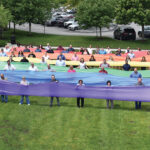 SUPPORTING INCLUSION: Cox Communications Inc. employees hold colored cloth to support the gay, lesbian, bisexual and transgender community.