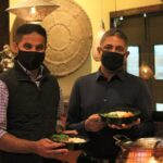 INDIA RESTAURANT in Providence is offering 100 free meals per day throughout December to help people who are impacted by the COVID-19 pandemic. Pictured, from left, are manager Ajay Vinoben and owner Amar Singh. / PBN PHOTO/JAMES BESSETTE