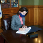 GOV. GINA M. RAIMONDO signs the fiscal 2021 state budget on Monday. / COURTESY R.I. GOVERNOR'S OFFICE