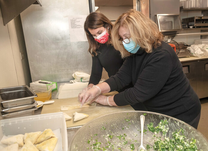 NEW TASKS: Alexandria Kitsilis Cardoso, left, and Christine Kitsilis, co-owners of Angelo's Palace Pizza in Cumberland, prepare food in the kitchen. Restaurant employees were cross-trained to become delivery drivers or cooks to keep them working when dining room sales dropped due to the COVID-19 pandemic. / PBN PHOTO/MICHAEL SALERNO