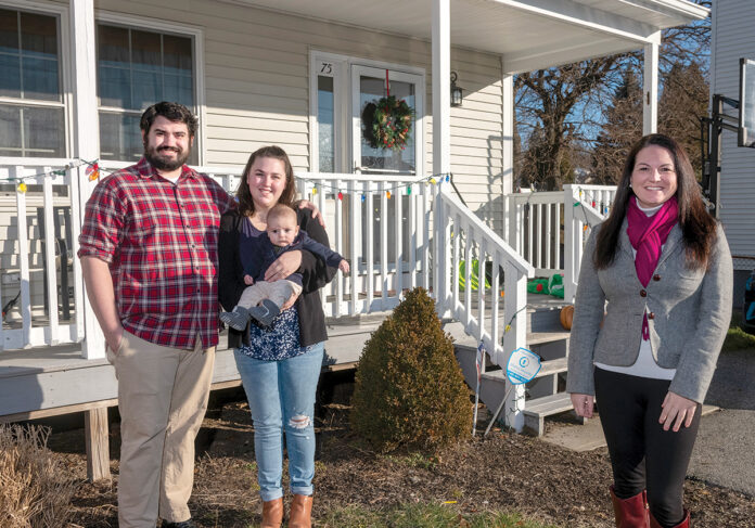 NEW HOME: Michael and Phoebe Koval, with their 4-month-old son, Barry, in front of their new home. The couple was renting a one-bedroom apartment in Providence before deciding to purchase a single-family property in the city's North End. At right is their real estate agent, Shannon Buss, broker associate at Randall Realtors.  PBN PHOTO/MICHAEL SALERNO