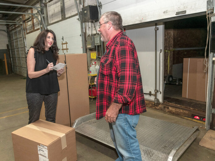 ALL-IN: Christine Soave Crum, left, owner of Gentry Moving and Storage in Cranston, accepts a delivery of office furniture from Don Erickson of Aspen Transport Service. Crum worked full time as a teacher when she founded the moving company with a partner in 2005 but now focuses all of her attention on Gentry. / PBN PHOTO/MICHAEL SALERNO