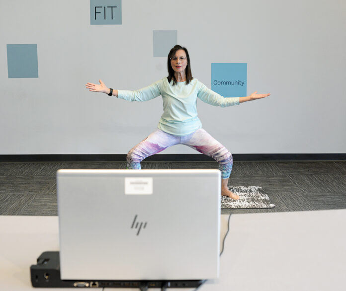 STAYING CONNECTED: Yoga instructor Jackie Hattoy leads a virtual yoga class on Jan. 21 at Blue Cross & Blue Shield of Rhode Island's Your Blue Store in Cranston. By the end of 2020, the health insurer had recorded 180 online yoga sessions and its video engagement had increased by 3,000% over the prior year. / PBN PHOTO/ELIZABETH GRAHAM