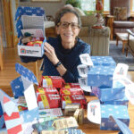 MEANINGFUL GIFTS: Giving Beyond the Box owner Sandra Enos assembles a themed gift box with items from social enterprises. / PBN PHOTO/ELIZABETH GRAHAM