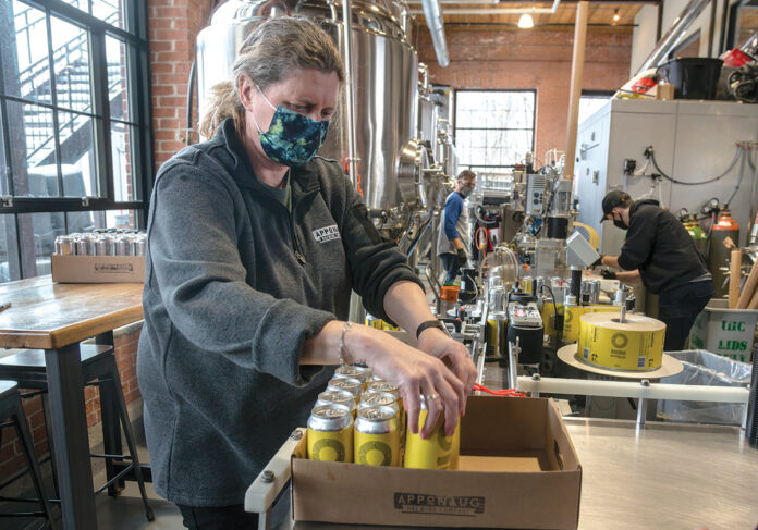 EYEING SPRING: Warwick's ­Apponaug Brewing Co. is hoping spring will bring crowds back to a large outdoor patio. Above, foreground, is co-owner Kris Waugh. / PBN FILE PHOTO/MICHAEL SALERNO